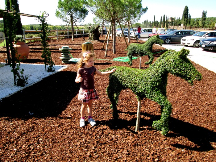 Lulu enchanted by Villa Sesta Polo Club's topiary ponies.
